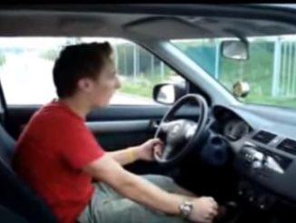自分の車でエア運転をする男性